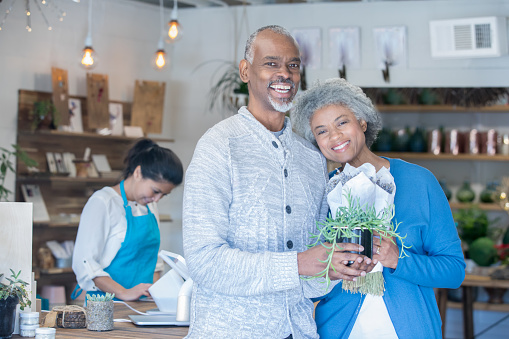 Senior African American couple shopping for plants in local gardening or flower store