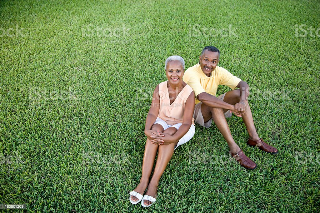 Senior African American couple sitting on grass together stock photo