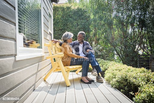 They are sitting on a yellow bench on the decking together outdoors in the garden