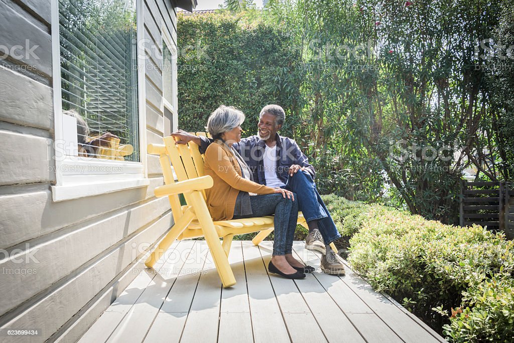 Senior African American couple sitting on porch outside house stock photo