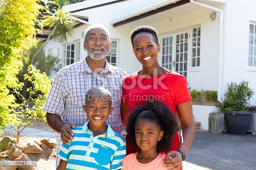 Happy senior African American couple with their grandson and granddaughter in the garden on a sunny day, smiling and looking to camera, at home spending quality time together.