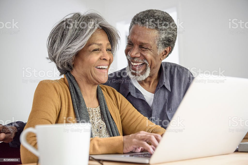 Senior African American couple using laptop and laughing stock photo