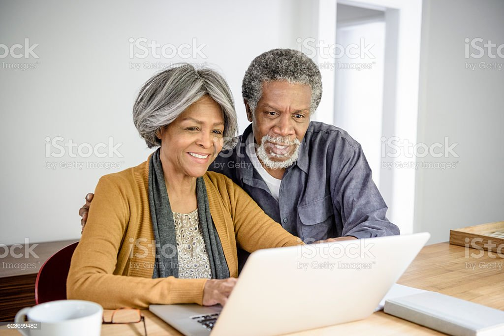 Senior African American couple using laptop together at home stock photo