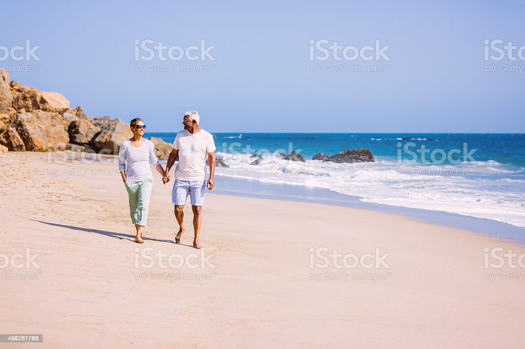Senior African American couple walking on beach stock photo