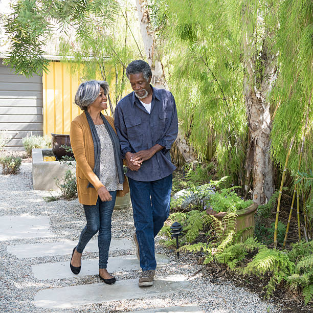 senior african american couple walking on garden path - 60 69 years stock photos and pictures