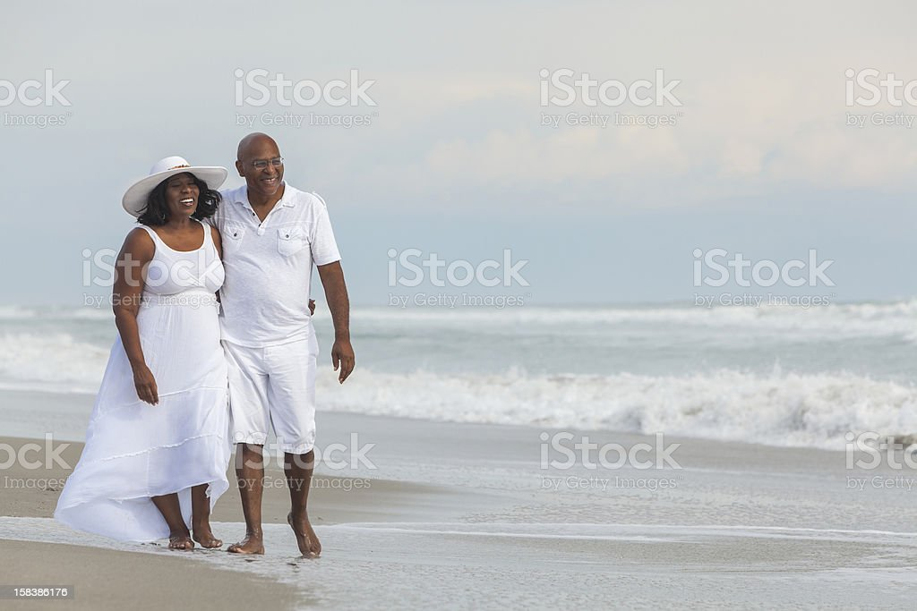 Senior African American couple walking on the beach stock photo