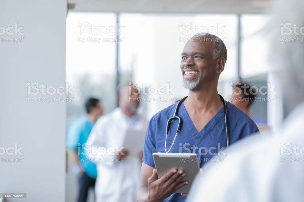 Senior African American doctor holds electronic medical record as he...
