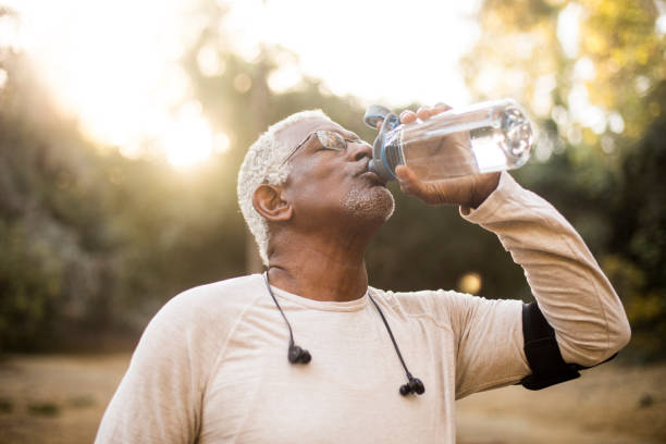 senior african american man drinkwater - water drinken stockfoto's en -beelden