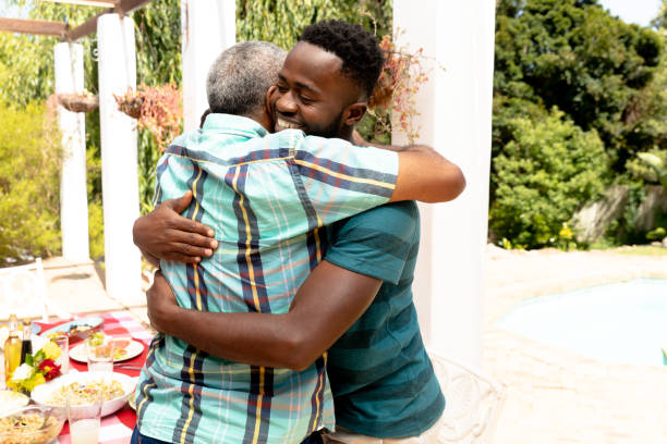 Senior African American man embracing with his son during a family lunch in the garden stock photo