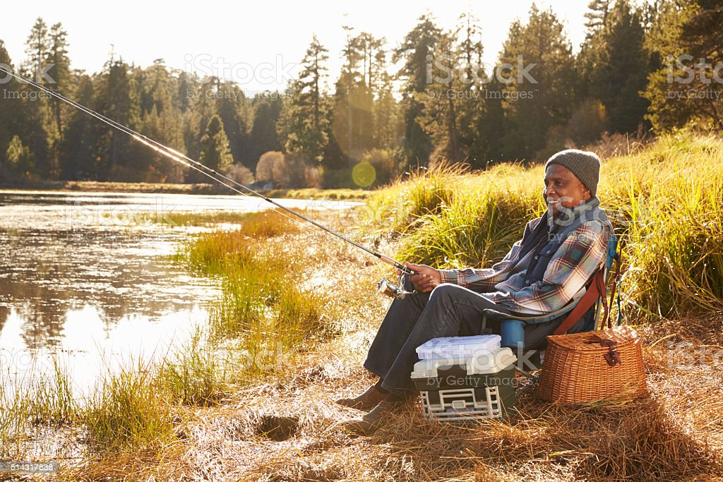 Senior African American Man Fishing By Lake stock photo