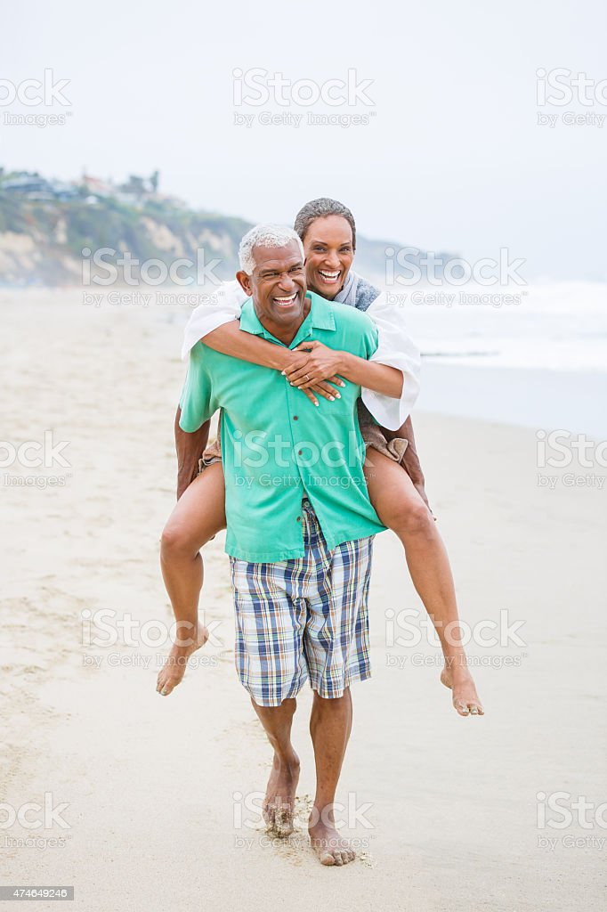 Senior African American man piggybacking his wife at beach stock photo