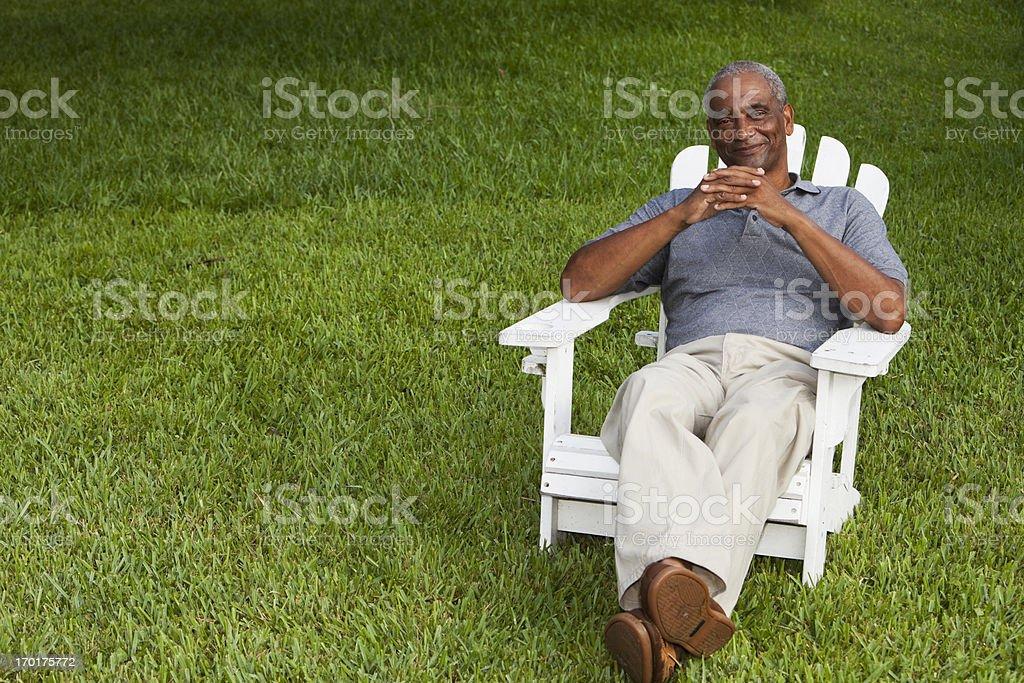 Senior African American man sitting in adirondack chair stock photo