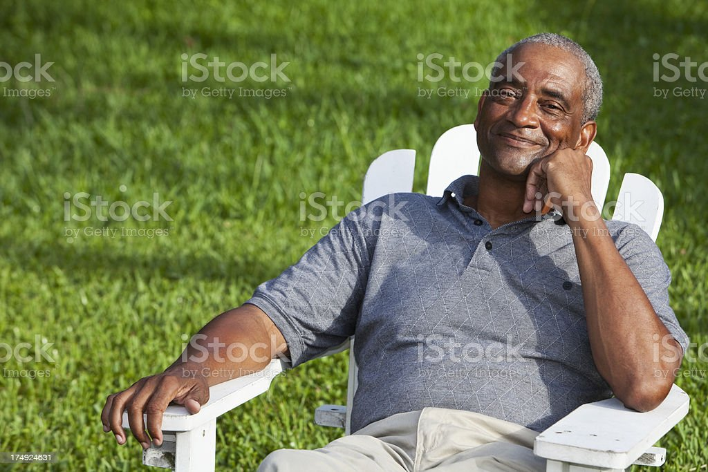Senior African American man sitting in adirondack chair royalty-free stock photo