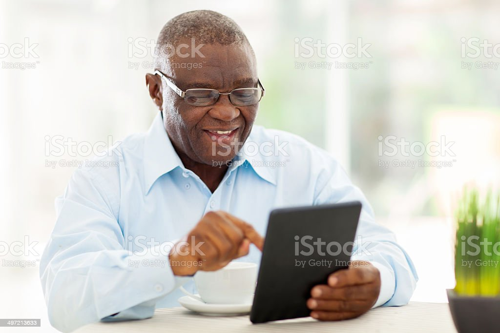 senior african american man using tablet computer at home stock photo