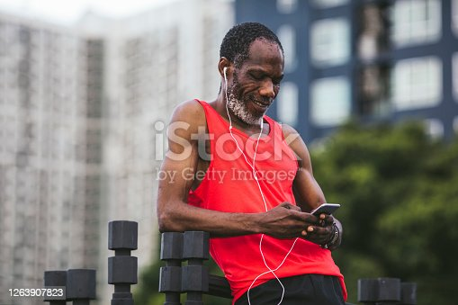 Citty runners: a mature man in red sportswear wearing earphones during an outdoor jogging session.