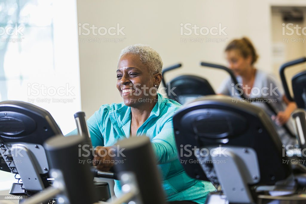 Senior African American woman at gym on exercise bike stock photo