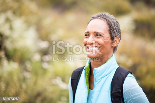 A senior african american woman backpacking and exploring