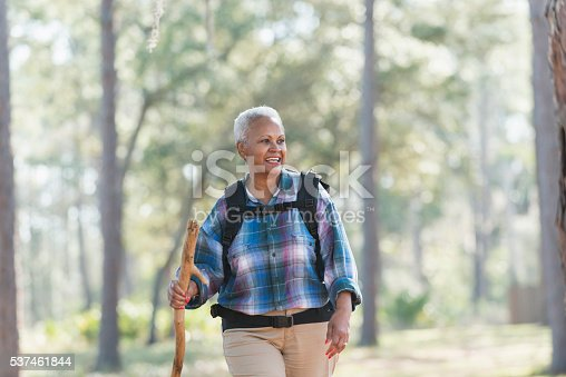 A senior African American woman carrying a backpack and walking stick, hiking through the woods.