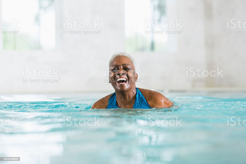 Senior African American woman in swimming pool laughing stock photo