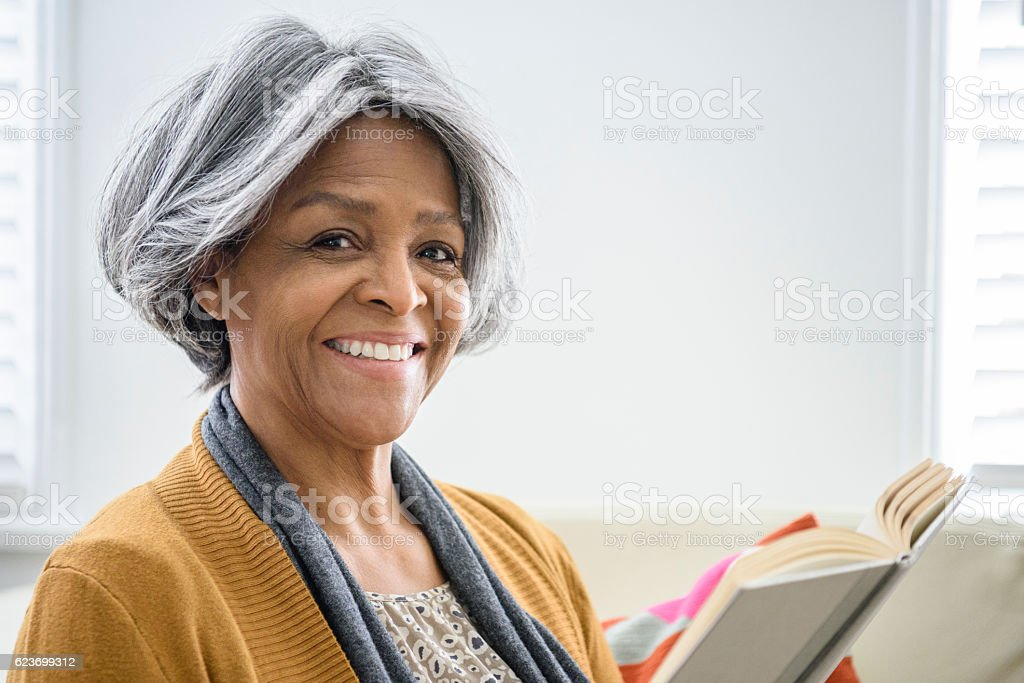 Senior African American woman smiling towards camera with book stock photo