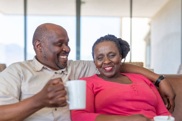 Senior African Couple at home Together on the Sofa stock photo