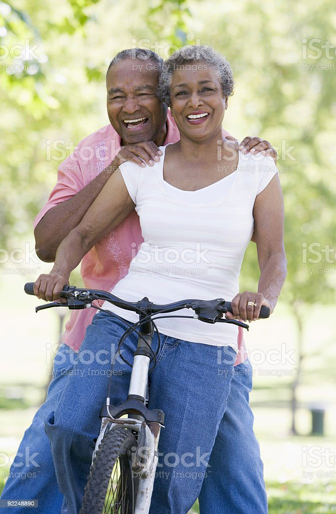 Senior African couple enjoying ride on a bike stock photo