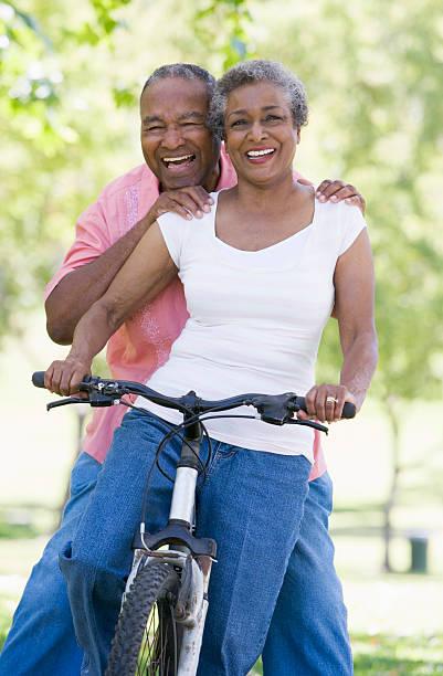 Senior African couple enjoying ride on a bike stock photo