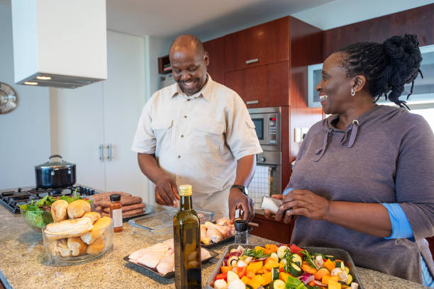 Senior African Couple Having Fun Cooking Together stock photo
