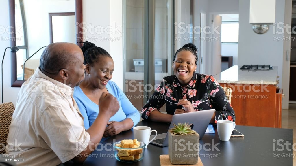Senior African couple signing their financial documents stock photo