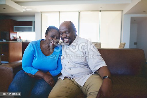 A Senior African Couple sitting on a leather sofa being in love smiling Strand Cape Town South Africa