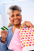 istock Senior African Descent female shopper with credit card gift bags 174855743
