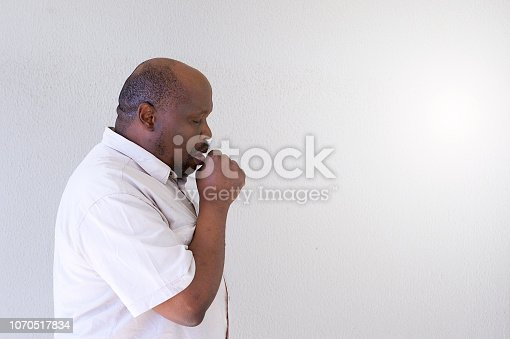 A Senior African male expressing emotions coughing side view against a blank white background wall Strand Cape Town South Africa