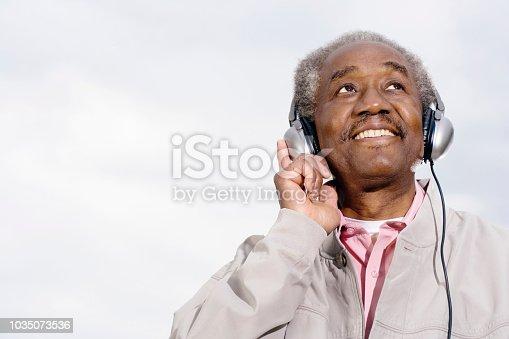Senior African man wearing headphones