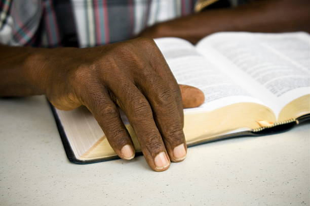 Senior African man's hand resting on the Bible. stock photo