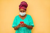 Senior african woman using mobile phone while wearing face protective mask for coronavirus prevention - Lifestyle, technology, ethnic and Covid 19 protections concept