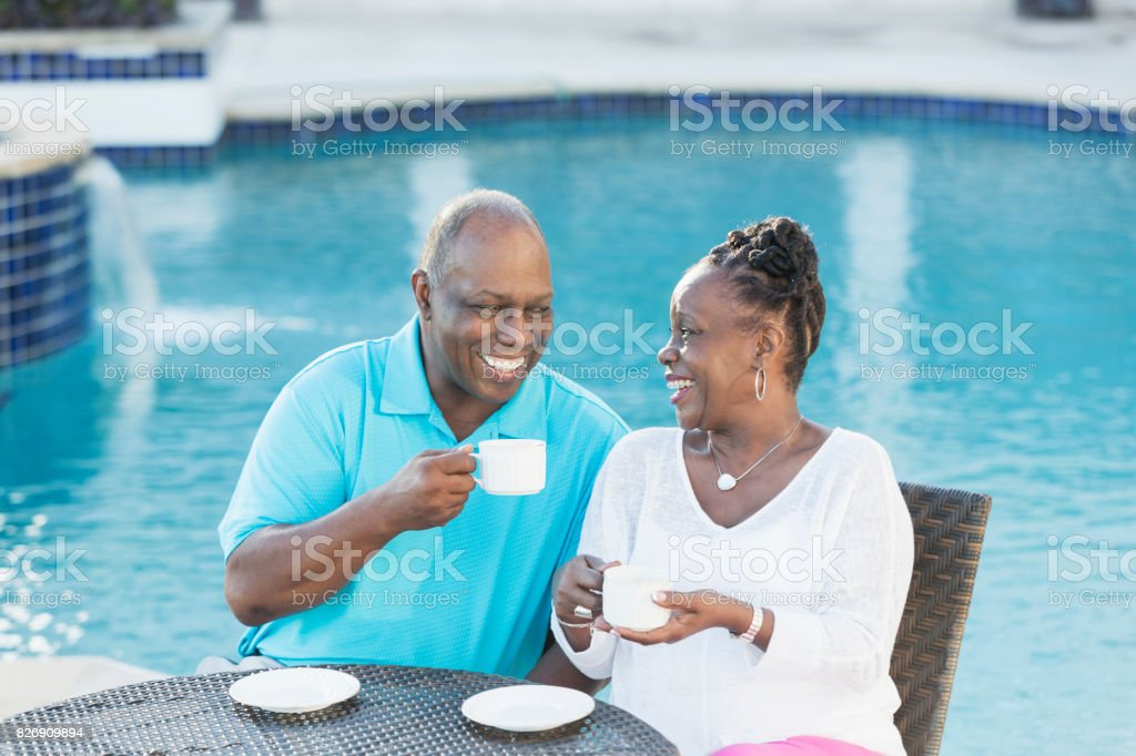 Senior African-American couple by pool drinking coffee stock photo