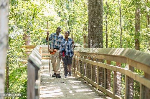 istock Senior African-American couple hiking, on footbridge 1023569238