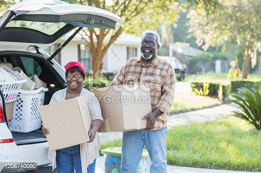 A senior African-American couple relocating, moving to a new home. They are excited, unloading boxes from their car. They are in their 70s, downsizing in retirement.