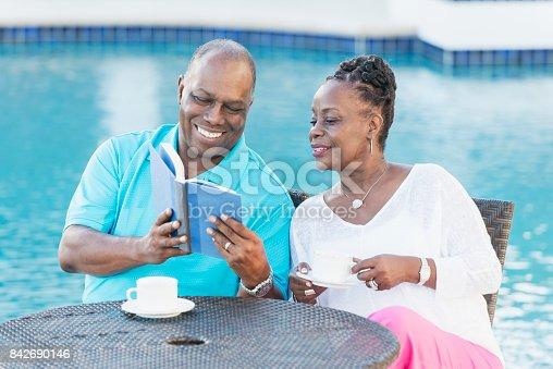 istock Senior African-American couple on pool deck, reading 842690146