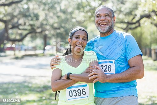 istock Senior African-American couple running race together 681903248