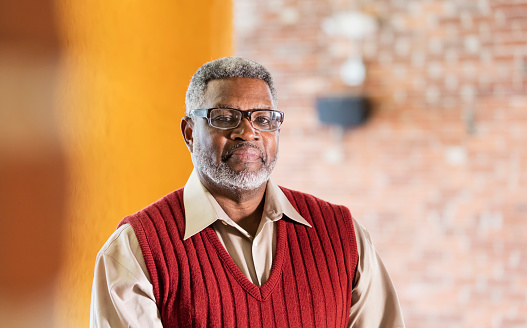 A senior African-American man in his 60s wearing eyeglasses, a button down shirt and sweater vest, standing indoors, looking at the camera with a serious, confident expression.