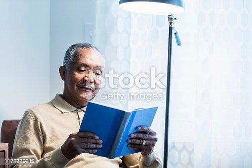 istock Senior African-American man reading book 1172339212