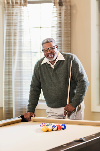 A senior African-American man in his 60s playing billiards. He is standing at one end of the pool table, holding a cue stick, ready to start the game.
