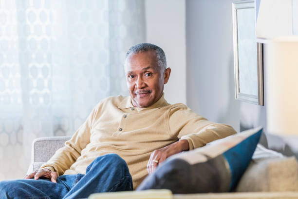 Senior African-American man sitting at home A senior African-American man in his 60s sitting on a sofa in his living room, smiling at the camera. He is relaxed, wearing casual clothing. 65 69 years stock pictures, royalty-free photos & images