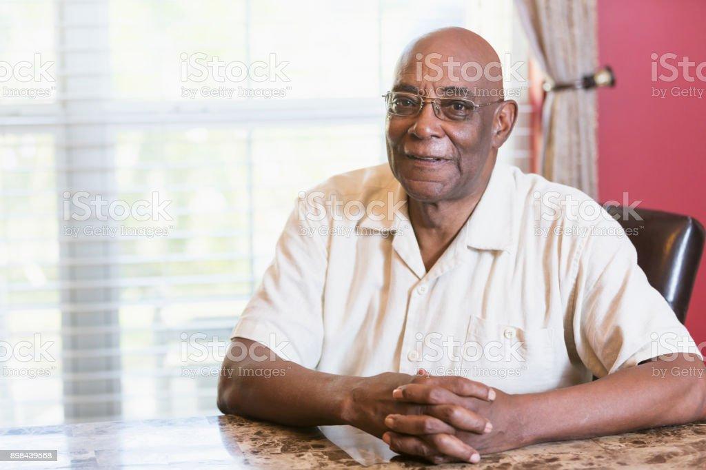 Senior afrikanisch-amerikanischer Mann sitzt am Tisch Fenster – Foto