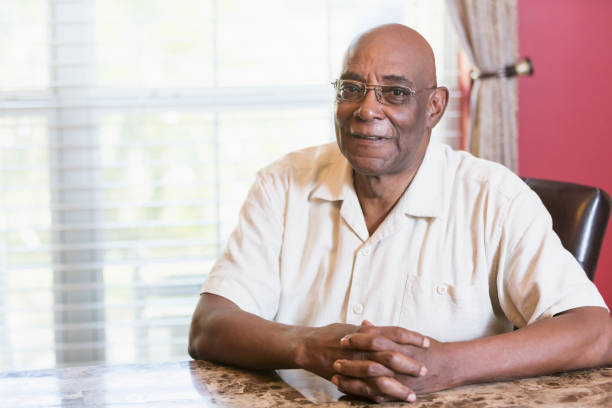 Senior African-American man sitting at table by window A senior African-American man in his 60s sitting at a table by a window with hands clasped, looking at the camera through eyeglasses. 65 69 years stock pictures, royalty-free photos & images
