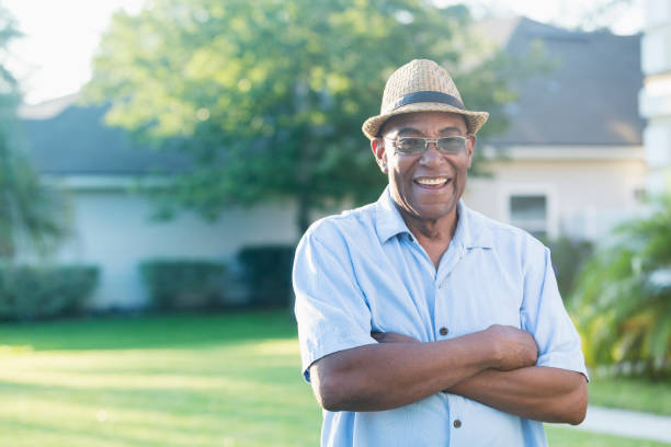 Senior African-American man standing in front yard A senior African-American man standing with his arms crossed in his front yard, smiling at the camera. He is relaxed and confident, wearing a stylish hat and eyeglasses. 65 69 years stock pictures, royalty-free photos & images