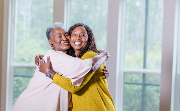 Senior African-American woman, adult daughter hugging stock photo