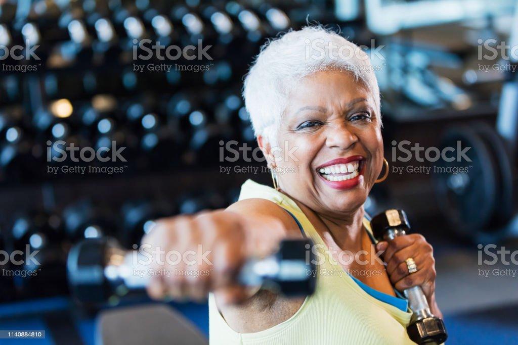Senior afro-amerikansk kvinna på gym lyfta hantlar - Royaltyfri 65-69 år Bildbanksbilder