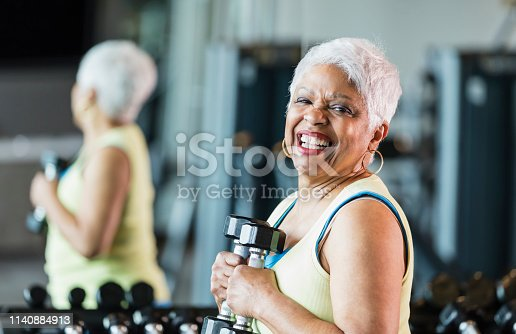 A senior African-American woman in her 60s working out at the gym, staying in shape. She is smiling at the camera, holding a dumbbell in each hand, in front of a rack of weights.